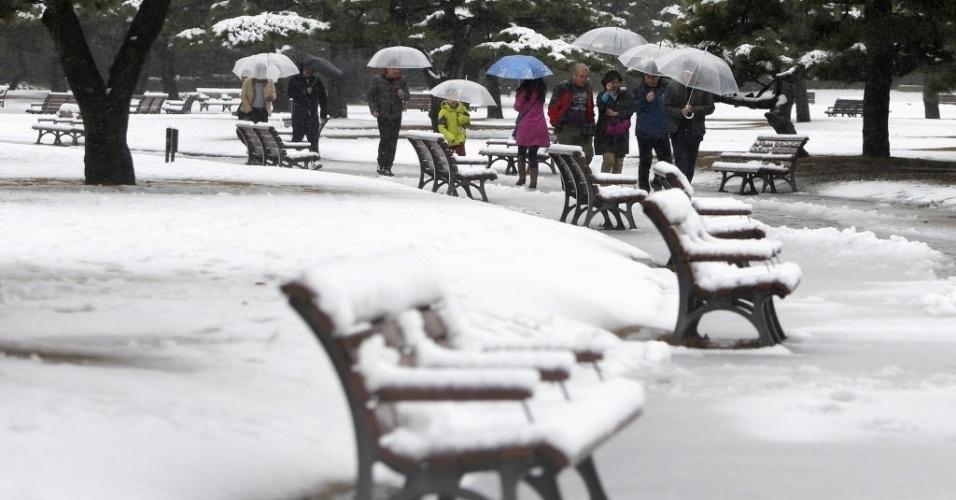 18.jan.2016 - Pessoas usam guarda-chuva para se protegerem da neve em praça próximo ao Palácio Imperial de Tóquio, no Japão. As fortes nevascas registradas durante a noite deixaram pelo menos 120 feridos no leste e no nordeste do Japão. Mais de cem voos nacionais foram cancelados e várias linhas de trens tiveram atrasos