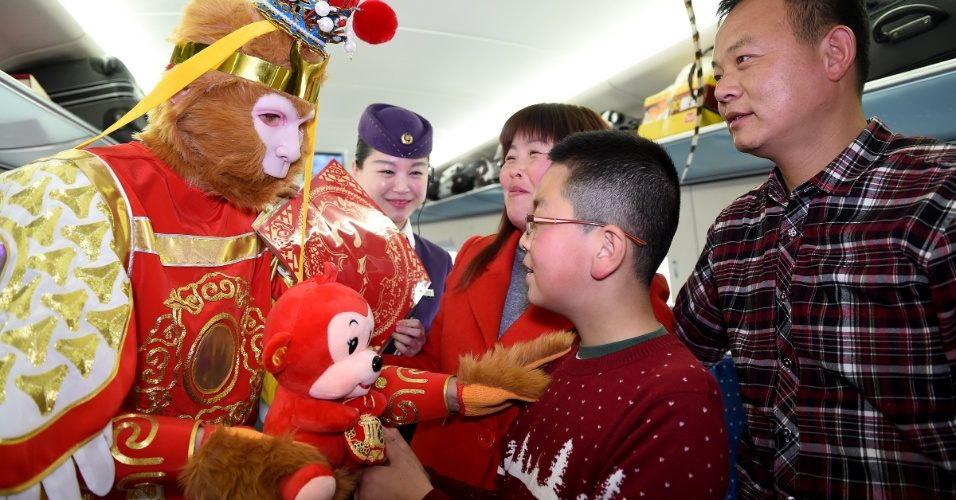 5.fev.2016 - Jovem ganha macaco de pelúcia de tripulante fantasiado em trem na província de Anhui, no leste da China. Diversas atividades têm sido realizadas para celebrar a chegada nos próximos dias do Ano-Novo lunar chinês, que será o ano do macaco