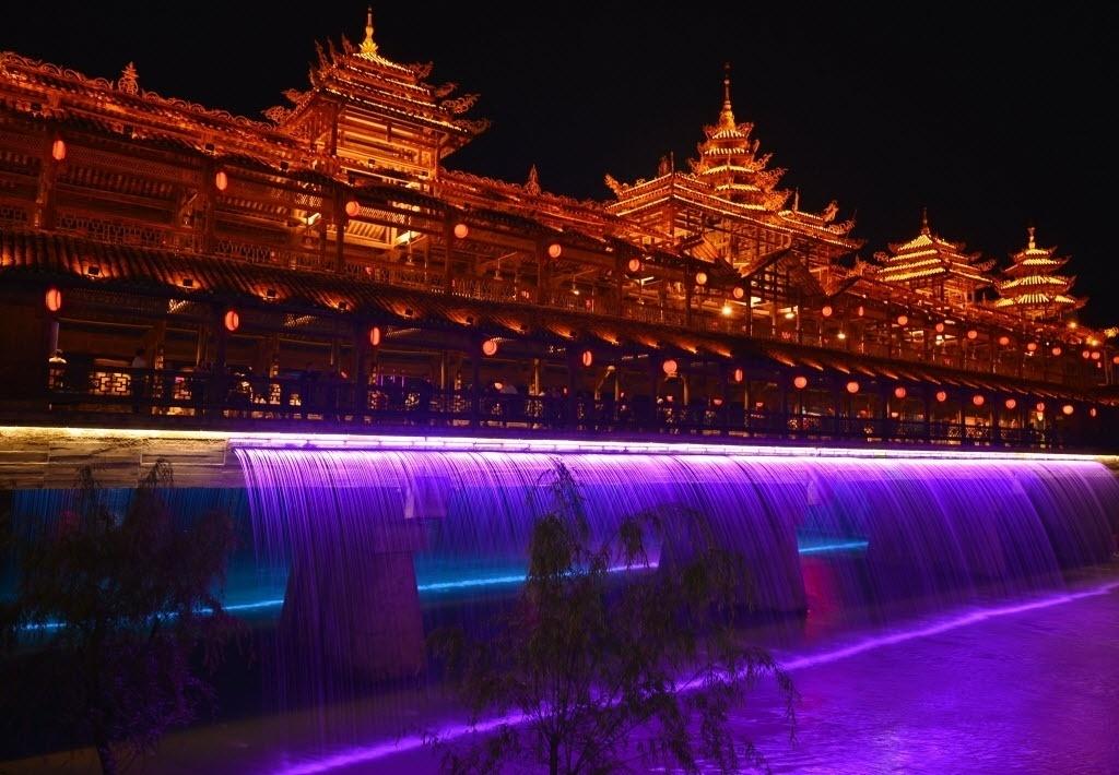 22.mai.2016 - Água circula em cascata próxima a prédios do grupo étnico Tujia, em Xuan'en, China, neste sábado