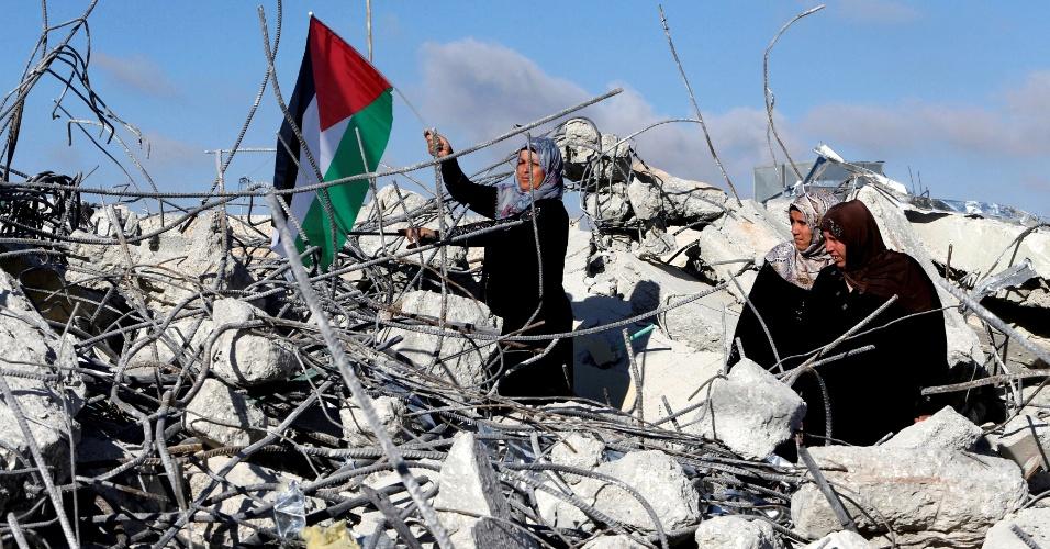 11.jun.2016 - A mãe do palestino Murad Idais, acusado de atacar a facadas uma israelense em um assentamento na Cisjordânia, ergue uma bandeira palestina em meios aos escombros de sua casa, demolida pelas forças israelenses na aldeia de Yatta, ao sul de Hebron. Idais foi baleado e morto em seguida ao ataque