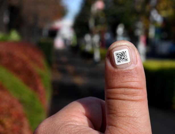 Funcionário da prefeitura mostra código QR na unha próximo à cidade de Iruma, Saitama (Japão)