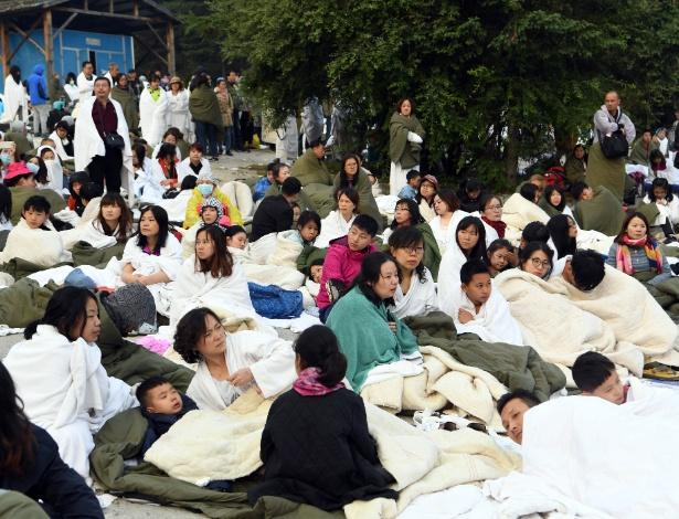 Turistas aguardam resgate no estacionamento de um resort no distrito de Jiuzhaigou