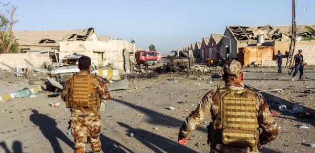 Integrantes de força de segurança trabalham nos escombros em Kirkuk após explosão
