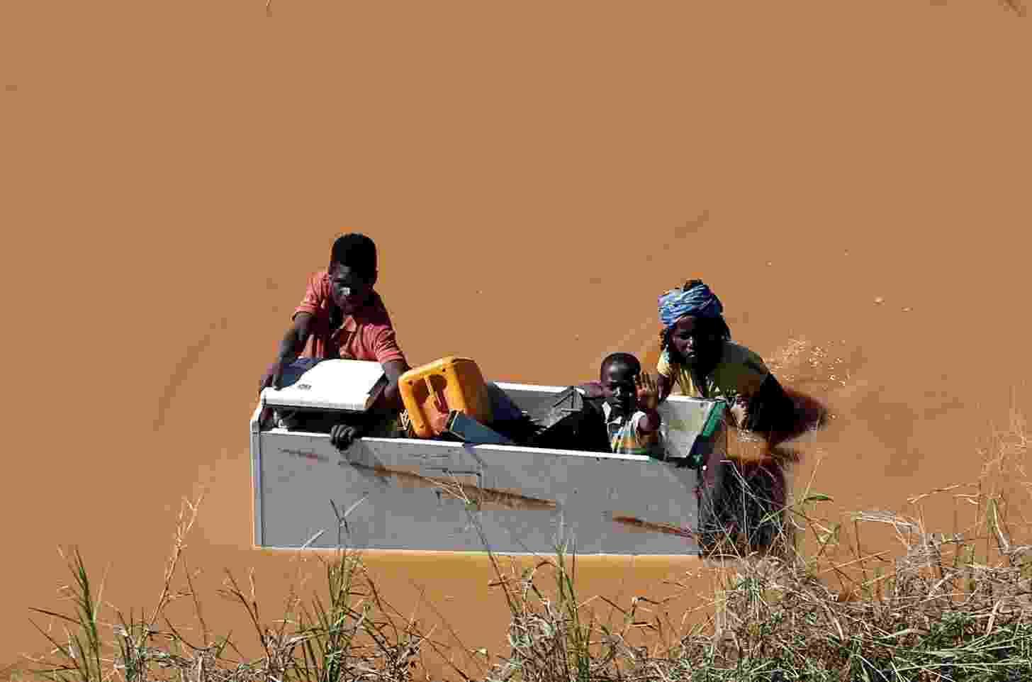 21.mar.2019 - Criança é transportada dentro de uma geladeira durante as inundações causadas pelo ciclone Idai, em Buzi, Moçambique - Siphiwe Sibeko/Reuters