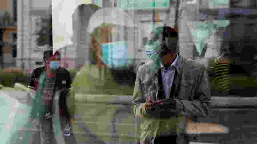 A imagem de um homem que espera em um ponto de ônibus é refletida em uma janela de ônibus, enquanto o país facilita o bloqueio devido à disseminação da doença por coronavírus (COVID-19), na estação Cais do Sodre, em Lisboa, Portugal - RAFAEL MARCHANTE/REUTERS