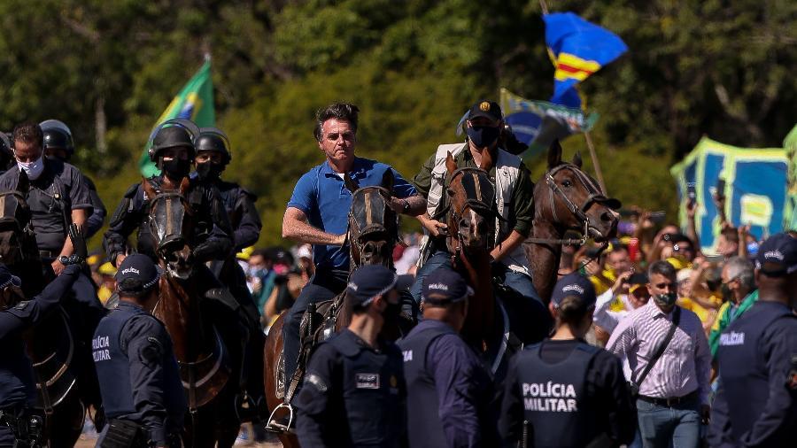 31-05-2020, 12h00: O presidente Jair Bolsonaro cumprimenta apoiadores na frente do Palácio do Planalto e depois dá uma volta em um cavalo da PM, durante uma manifestação em apoio ao governo. - Pedro Ladeira/Folhapress