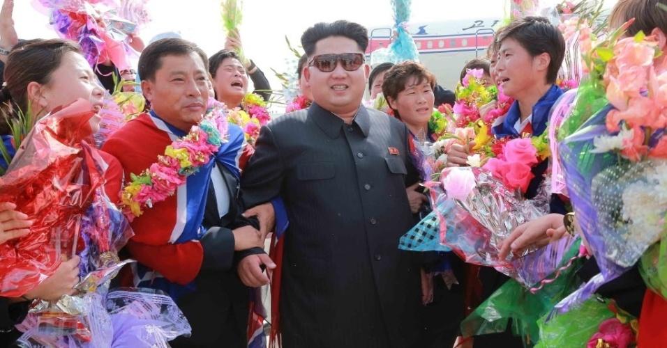11.ago.2015 - O ditador da Coreia do Norte, Kim Jong Un, cumprimenta jogadoras equipe de futebol feminino do país durante a chegada no aeroporto internacional de Pyongyang, após ganharem Copa do Leste da Ásia