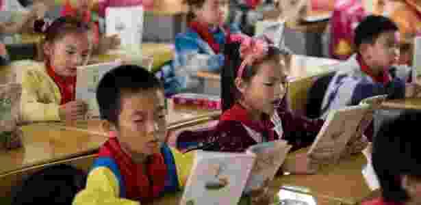 9.out.2015 - Crianças leem livros em escola primária do condado de Pingjiang, província de Hunan, China, no primeiro dia de volta às aulas - Johannes Eisele/AFP