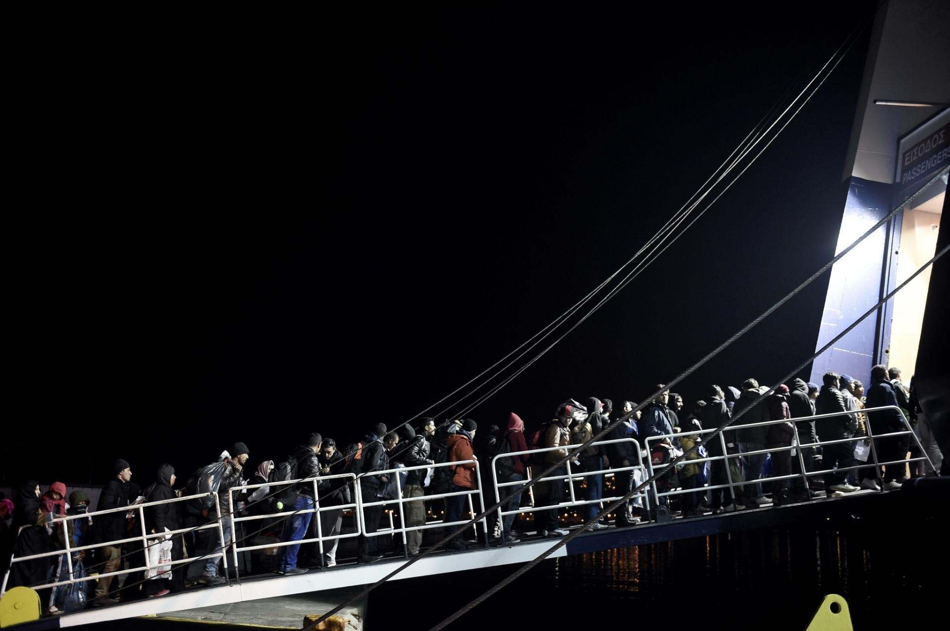 8.dez.2015 - Em busca de luz no fim do túnel, refugiados entram em balsa no porto de Mytiline, em Lesbos, na Grécia, após chegarem oriundos da Turquia. O dia teve mais uma tragédia nas águas da região: pelo menos seis crianças morreram quando um bote com migrantes afegãos afundou a caminho da Grécia, segundo a imprensa local