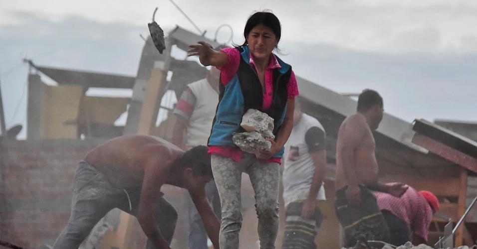17.abr.2016 - A equatoriana Veronica Paladines remove destroços em busca de seu marido, em Manta, no Equador
