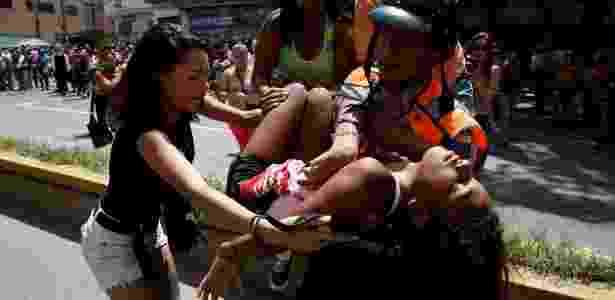 Imagem de arquivo mostra policial carregando uma mulher que desmaiou durante confusão para tentar comprar massas fora de um supermercado em Caracas, Venezuela - Carlos Garcia Rawlins/Reuters