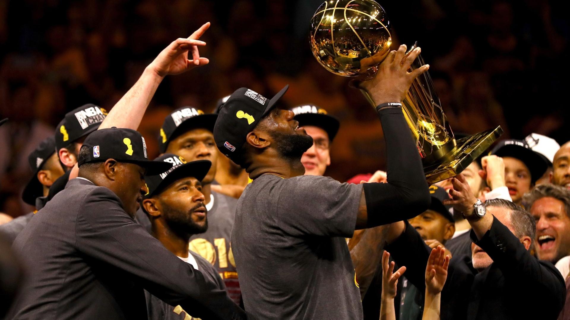 20.jun.2016 - O jogador LeBron James, do Cleveland Cavaliers, ergue o troféu da NBA que a equipe recebeu após ser campeã da edição deste ano da liga profissional de basquete norte-americana. LeBron foi um dos destaques na vitória do Cavaliers sobre o Golden State Warriors por 93 a 89, fechando a sequência final de partidas do campeonato em 4 a 3