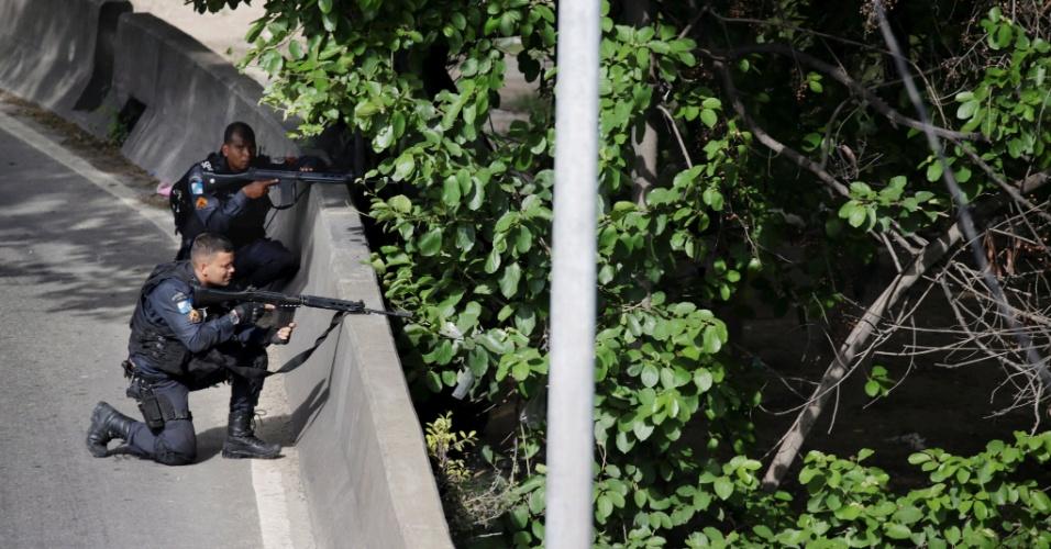 1º.fev.2018 - Policiais militares se escondem atrás da mureta da Linha Amarela, na zona oeste, e trocam tiros com criminosos da Cidade de Deus