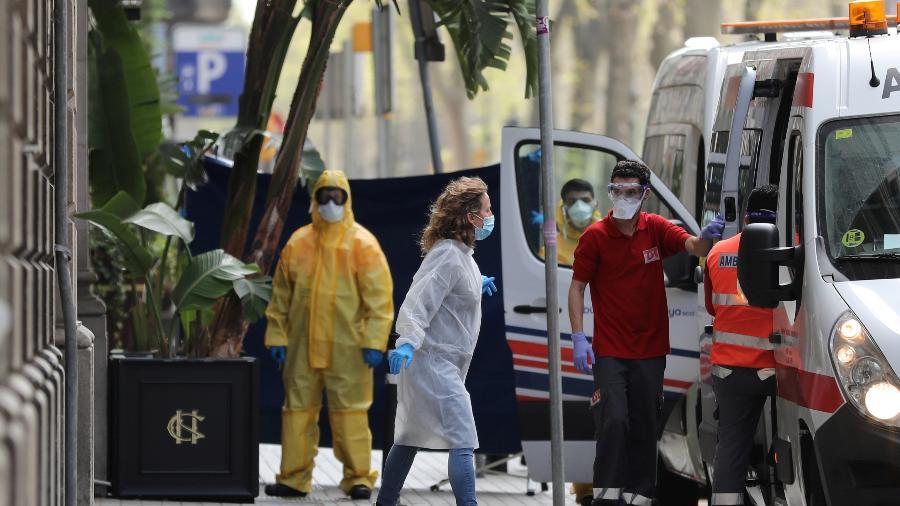 Profissionais da saúde são vistos do lado de fora do Cotton House Hotel, preparado para acomodar pacientes com sintomas leves ou assintomáticos do novo coronavírus - Nacho Doce/Reuters
