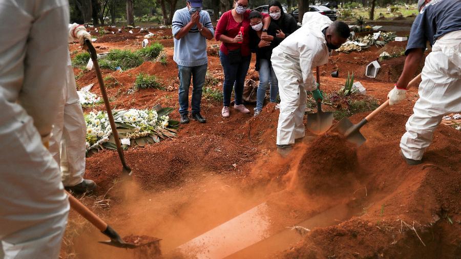 Parentes assistem a coveiros vestindo roupas de proteção enterrando o caixão de um homem que morreu da doença por coronavírus (COVID-19), no cemitério de Vila Formosa - AMANDA PEROBELLI/REUTERS