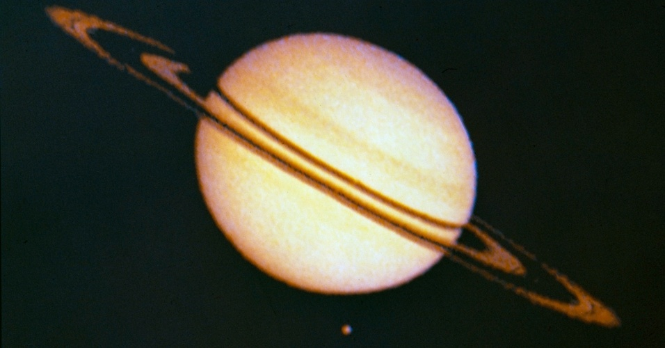 27.ago.2015 - A primeira espaçonave a sobrevoar Saturno foi a Pioneer 11, em 1979. Mas só em 2004, após quatro anos de jornada rumo ao planeta, a espaço nave Cassini-Huygens foi a primeira a orbitar Saturno. A sonda Huygens aterrissou em Titã com sucesso em 2005, revelando detalhes sobre a superfície do satélite. A missão continua em plena atividade e deve se estender até 2017 quando haverá o solstício no planeta. A imagem  foi feita pela Pioneer 11 em 1979 e mostra Saturno e a sua maior lua, Titã