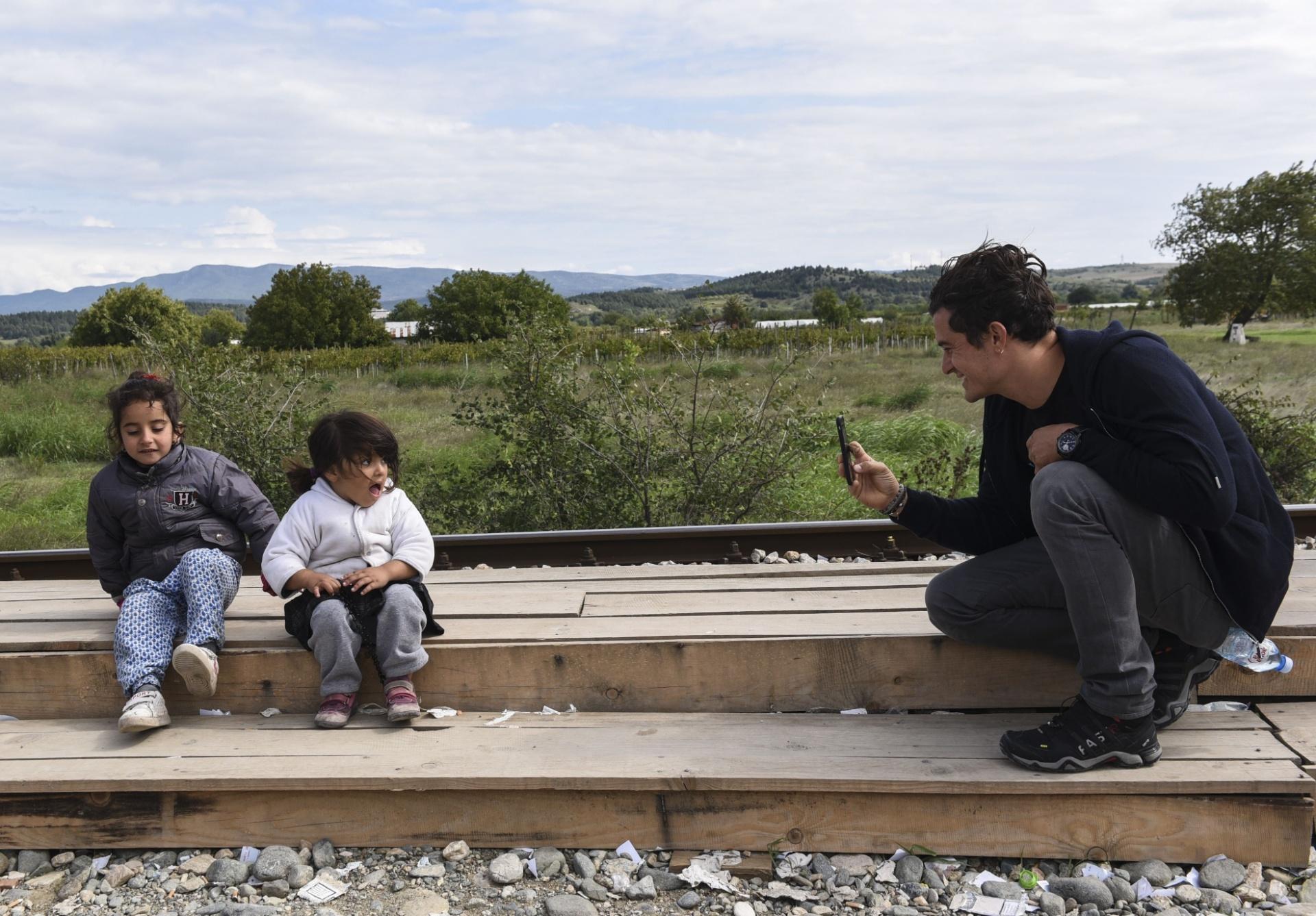 28.set.2015 - O ator britânico Orlando Bloom, embaixador da Boa Vontade do Unicef, tira fotografia de crianças em visita a campo de refugiados em Gevgelija, Macedônia