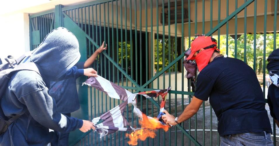 15.out.2015 - Manifestantes queimam uma bandeira do Estado de São Paulo no portão do Palácio dos Bandeirantes no começo da tarde desta quinta (15). Estudantes e professores protestam contra a reorganização da rede estadual de ensino anunciada em setembro pela Secretaria da Educação. Eles temem o fechamento de escolas no processo