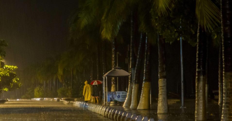24.out.2015 - Vestindo capa de chuva, pessoas caminham por avenida de Puerto Vallarta, na costa oeste do México, durante passagem do furacão Patricia. Após ser classificado como o furacão mais forte já registrado, o Patricia perdeu força conforme avança pelo território mexicano em direção nordeste, porém continua perigoso, com ventos de até 260 km/h