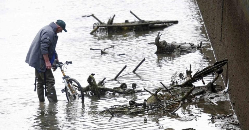 5.jan.2016 - Homem caminha pela água enquanto analisa estragos em bicicletas que apareceram durante a drenagem do canal Saint-Martin em Paris, na França. As autoridades começaram uma operação de limpeza que irá durar três meses, em uma tentativa de reformar os bloqueios e remover o lixo do canal