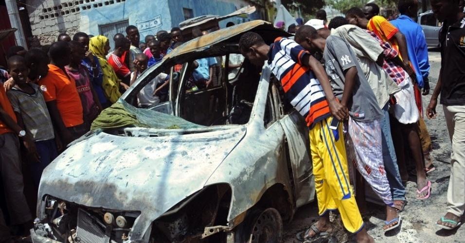 5.fev.2016 - Pessoas olham carro que explodiu em Mogadício, capital da Somália. Três pessoas morreram no atentado provocado pelo carro-bomba que tinha como alvo o aeroporto da capital do país