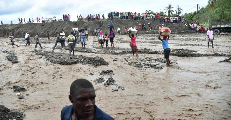 6.out.2016 - Moradores cruzam rio La Digue em Petit Goave depois que a ponte caiu durante a passagem do furacão Matthew, no Haiti