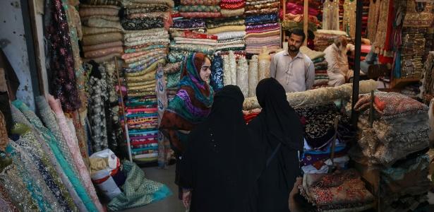 Mulheres compram tecidos roupas para casamento em loja de Karachi