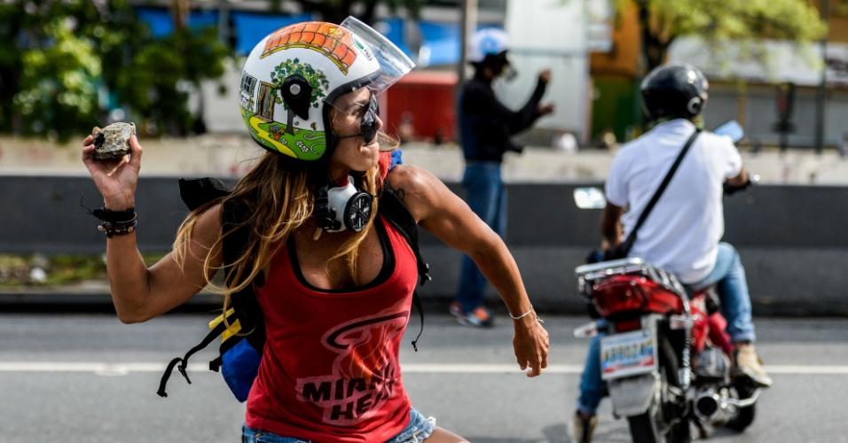 """1º.mai.2017 - Com pernas musculosas e uma pedra nas mãos, pronta para ser jogada contra os policiais, a instrutora de fitness Caterina Ciarcelluti ganhou o apelido de Mulher Maravilha depois da foto de Federico Parra. """"Você sempre está procurando por algo que se sobressaia e então de repente, entre 20 caras mascarados, deparei com essa estereótipo da beleza venezuelana"""", conta Parra. """"Essa sou toda eu, a força e a paixão"""", disse Ciarcelluti, 44. Ela espera servir de """"inspiração"""" para outro manifestantes. """"Vamos chegar lá"""", disse."""