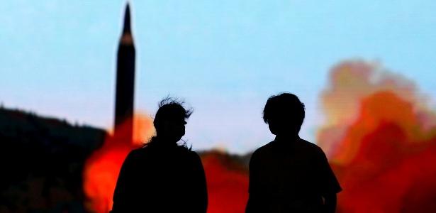 Pessoas caminham diante de tela com notícias sobre as ameaças da Coreia do Norte, em Tóquio, Japão