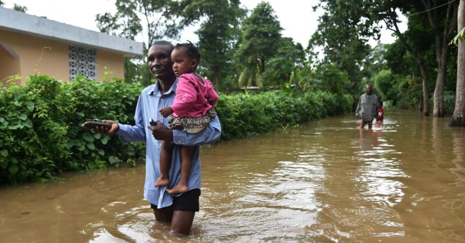 8.set.2017 - Com uma criança no colo, homem anda em meio a uma rua inundada de Fort Liberte, no nordeste do Haiti, após a passagem do furcão Irma