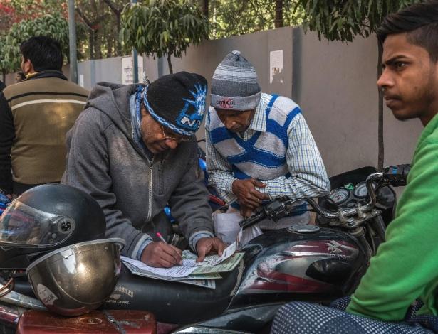 Indianos preenchem formulários em centro de registro do programa Aadhaar, em Nova Deli