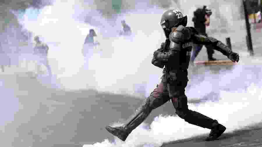 Policial chuta lata de gás lacrimogênio durante protestos em Santiago, no Chile - Edgard Garrido/Reuters