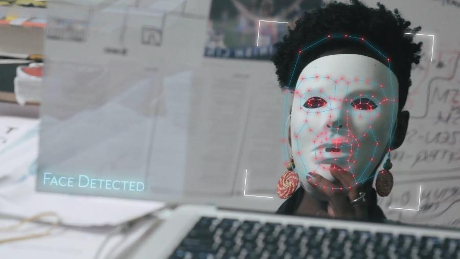 """Joy Buolamwini usa uma máscara para testar software de reconhecimento facial em cena do documentário """"Coded Bias"""" - Divulgação"""