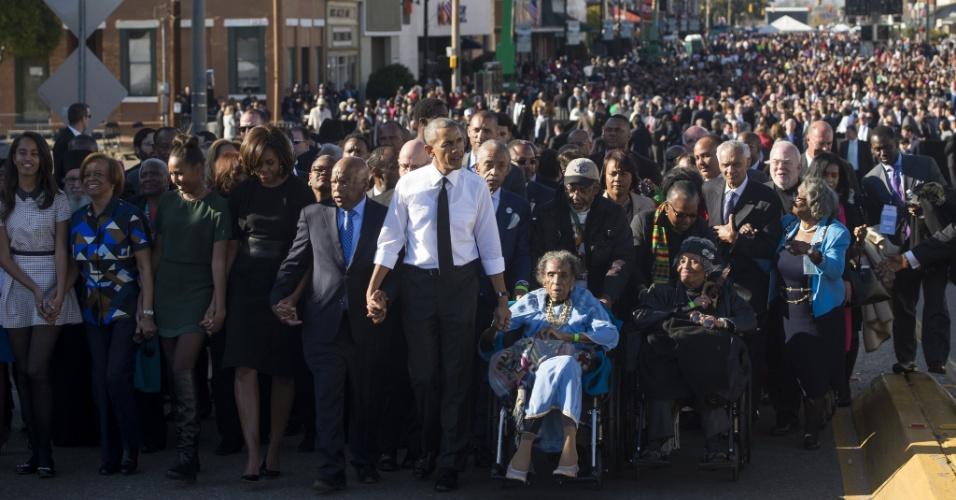 7.mar.2015 - Presidente dos EUA, Barack Obama (Centro) caminha ao lado de Amelia Boynton Robinson e de John Lewis (manifestantes originais), para marcar o 50º aniversário da marcha pelos direitos civis de Selma para Montgomery, no Alabama (EUA)
