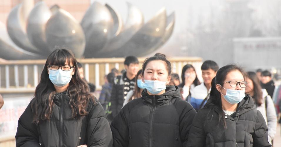 2.jan.2016 - Turistas usam máscaras enquanto caminham pela praça Quancheng, em Jinan, no leste da China. Um alerta amarelo foi emitido pela estação meteorólogica local devido ao nível de poluição do ar