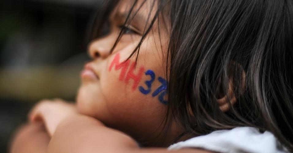 6.mar.2016 - Criança tem o rosto pintado com o número do voo da Malaysia Airlines durante um evento em Kuala Lumpur em memória dos passageiros mortos em acidente aéreo. O voo MH370 desapareceu no dia 8 de março de 2014 quando ia de Kuala Lumpur, na Malásia, a Pequim, na China, com 239 passageiros e tripulantes a bordo