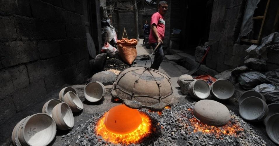 7.mai.2016 - Homem usa método tradicional para produzir potes em Zhijin, na China