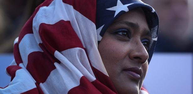 Mulher usa bandeira dos EUA como véu islâmico durante protesto contra decreto de Donald Trump que proíbe a entrada de refugiados nos EUA