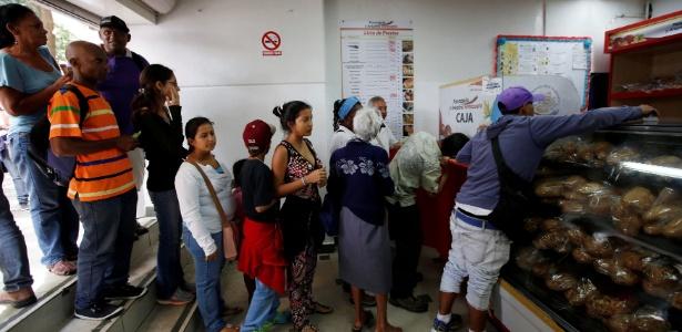 Moradores formam fila para comprar pão, em Caracas, na Venezuela