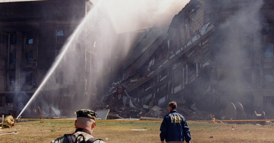 Os primeiros socorristas tentam apagar as chamas provocadas pela queda do avião da American Airlines usado no atentado contra o prédio do Pentágono, em Washington DC