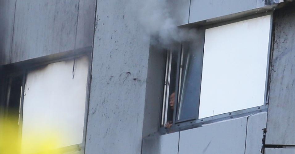 14.jun.2017 - Morador do prédio sofre com fumaça dentro se seu apartamento na Grenfell Tower, que pegou fogo nesta quarta-feira