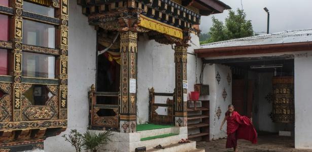 Um jovem monge entra no templo Chimi Lhakhang para as orações da manhã, perto de Lobesa, no Butão - Gilles Sabrié/The New York Times