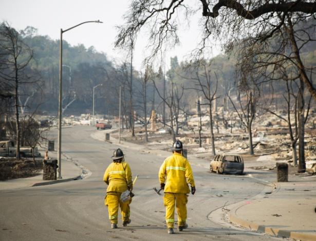 Bombeiros caminham em via deserta de moradias destruídas na cidade de Santa Helena - Elijah Nouvelage/Getty Images/AFP
