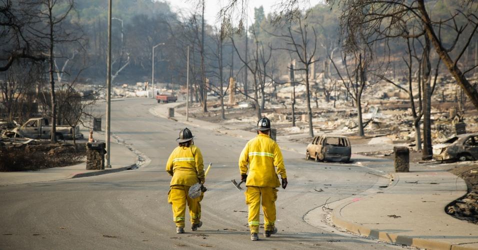 13.out.2017 - Bombeiros caminham em via da cidade de Santa Helena em meio a destruição provocada pelo incêndio florestal que atinge a Califórnia