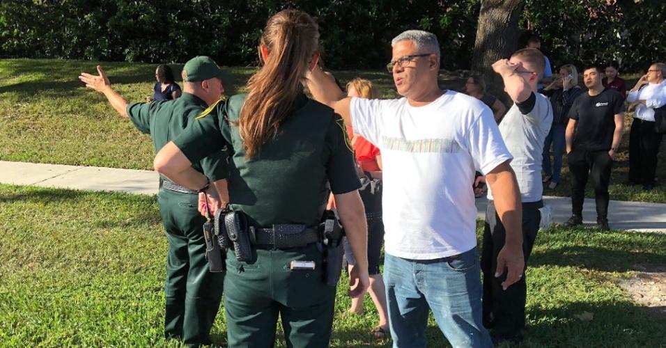 14.fev.2018 - Seguranças conversam com pessoas perto escola pública Marjory Stoneman Douglas, em Parkland, na Florida, após tiroteio