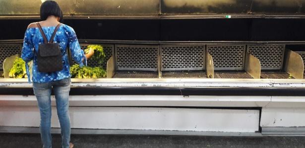 Mulher escolhe hortaliça em uma geladeira quase vazia em um supermercado de Caracas