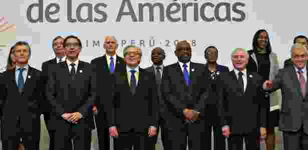 14.abr.2018 - Os presidentes da Argentina, Mauricio Macri, Peru, Martin Vizcarra, o secretário-geral da OEA, Luis Almagro, o premiê das Bahamas, Hubert Minnis, o presidente brasileiro Michel Temer, e o chileno Sebastián Piñera, posam durante a Cúpula das Américas, em Lima; ao fundo, o vice-presidente dos EUA, Mike Pence (Donald Trump não participou do evento) - Cris Bouroncle/AFP - Cris Bouroncle/AFP