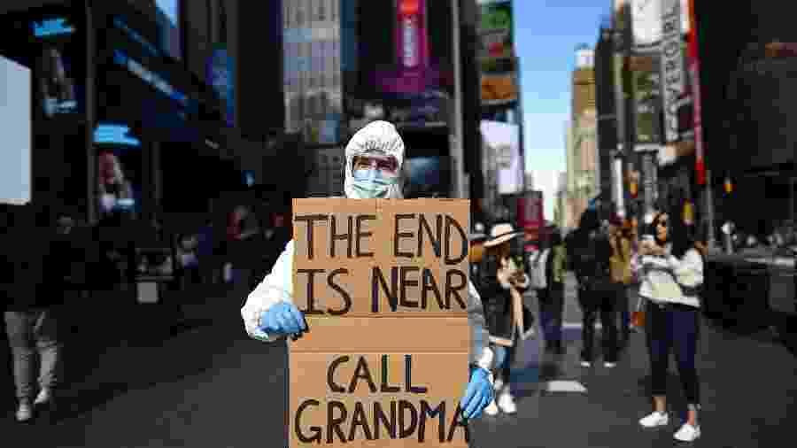 """""""O fim está próximo"""", diz manifestante em cartaz sobre coronavírus na Times Square, em Nova York (EUA) - Johannes Eisele/AFP"""
