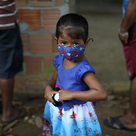 Criança com máscara protetora na Bela Vista do Jaraqui - BRUNO KELLY/REUTERS