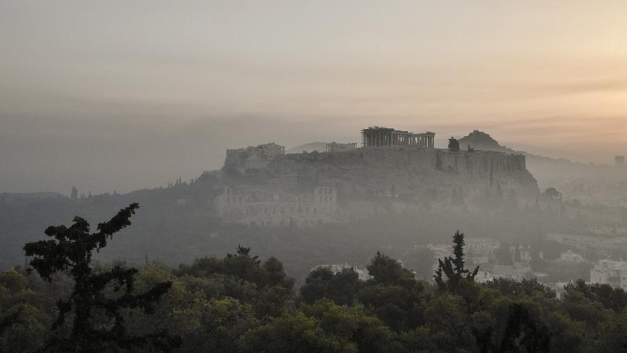 Fumaça cobre o centro de Atenas com a Acrópole ao fundo, devido aos incêndios no sopé do Monte Parnes, 30 quilômetros ao norte de Atenas - LOUISA GOULIAMAKI / AFP